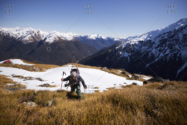 Man in the mountains striding through grass and snow with rifle and skis on his back