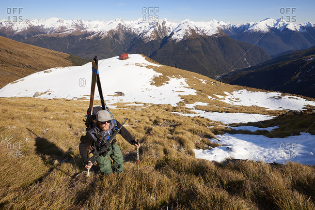 Man in the mountains walking through grass and snow with rifle and skis on his back
