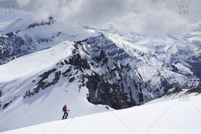 Girl skier looking out at cloudy mountains