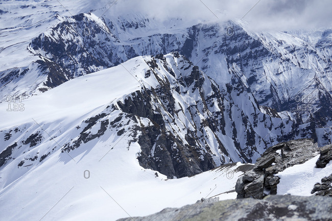 3 people ski touring with big and cloudy mountains in the back ground