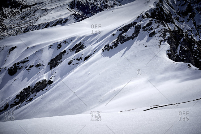 Skiing down a mountain slope in the backcountry with cloudy mountain ridges in the background