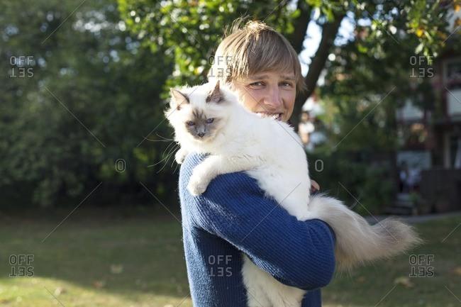 Pet owner holding white cat
