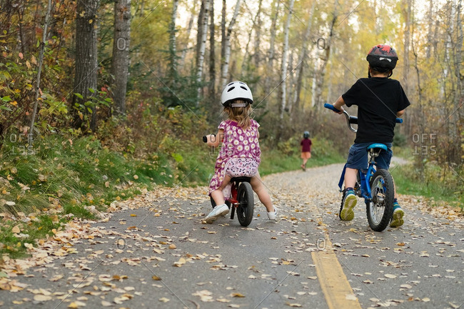 Two children on bicycles follow a third child on road in woods