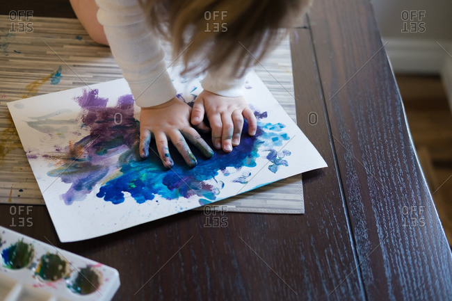Elevated view of child making a finger painting