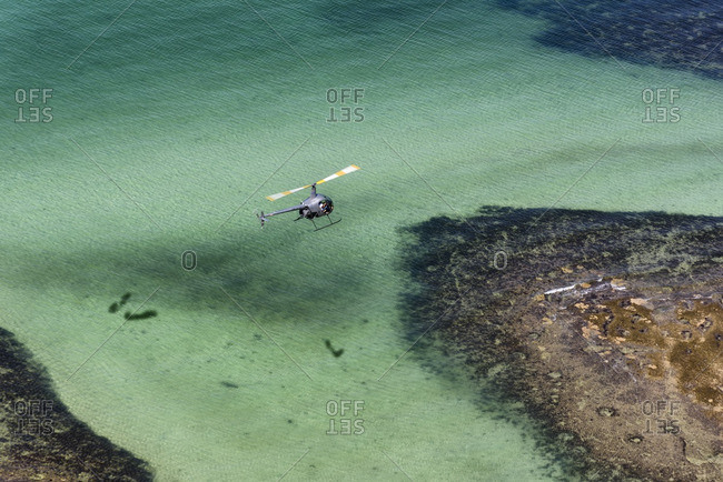 Salvador da Bahia, Brazil - July 8, 2016: Small sightseeing helicopter flying over coral reef