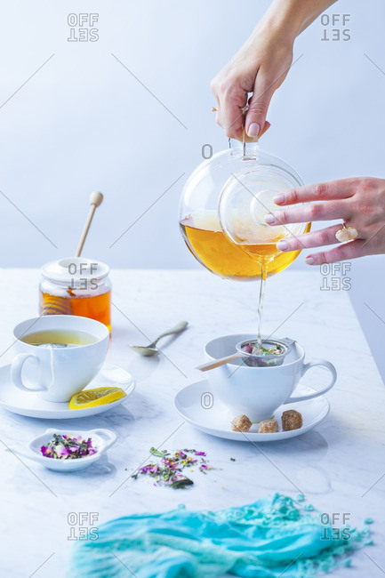 Woman pouring tea through strainer into teacup