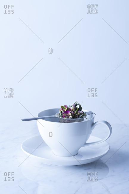 Loose herbal tea in strainer above teacup