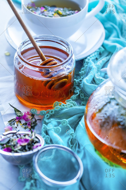 Jar of honey with teapot, teacup and herbal tea in strainer