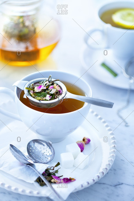 Cup of tea with loose tea in strainer and sugar cubes on saucer