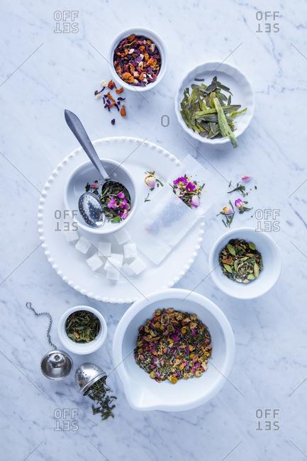 Arrangement of loose leaf teas on marble background