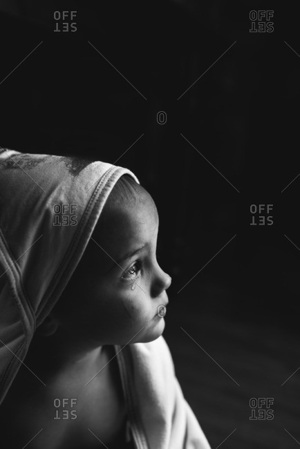Young child in a hooded bath towel with tear coming from eye
