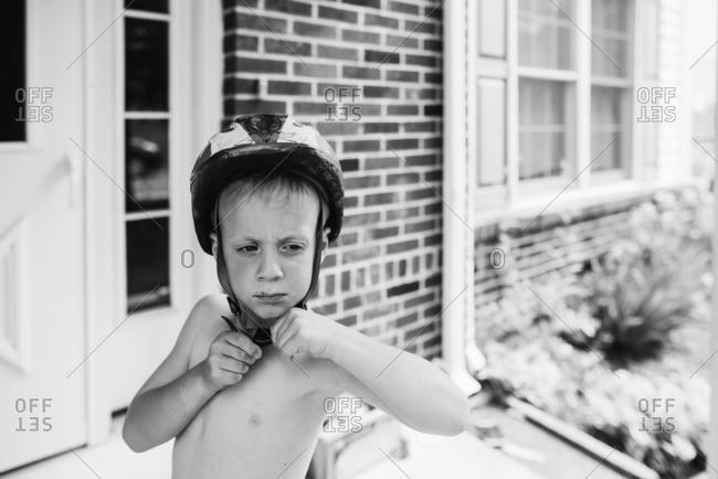 Shirtless boy buckles bike helmet on front porch