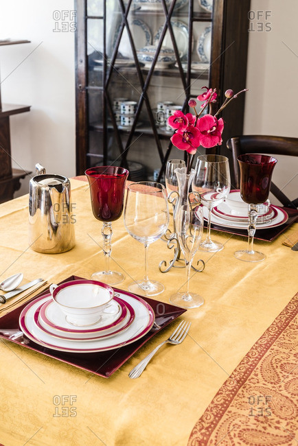 Contemporary place settings with drinking glasses, cups and saucers, and pitcher