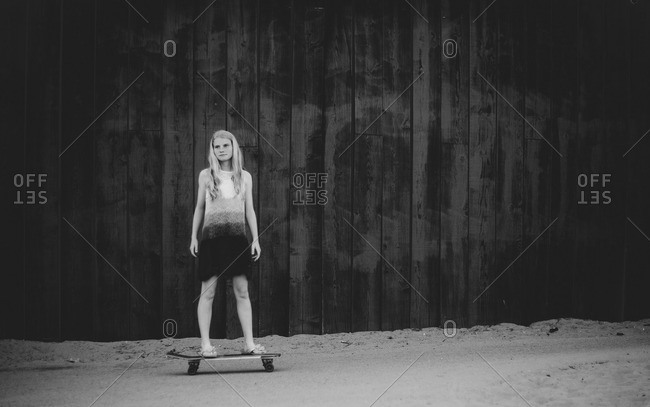 Teenage girl alone on skateboard with thoughtful look on her face in black and white