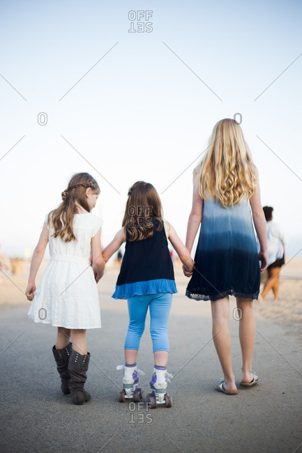 Two older sisters helping younger sister roller-skate on a sidewalk by the beach