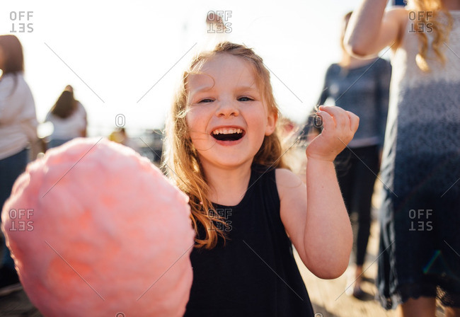 5 year old Caucasian girl eating pink cotton candy on a sunny day