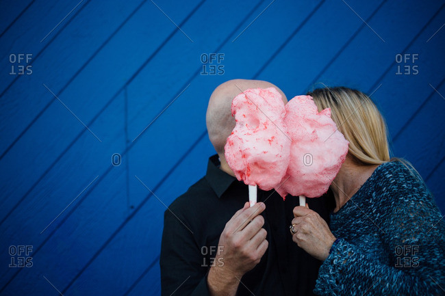 Man and a woman hiding behind pink cotton candy kissing in front of a blue wall