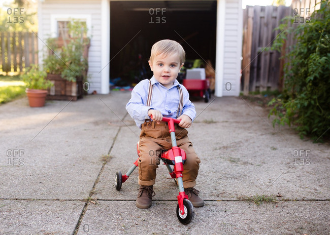 Boy sitting on a tricycle
