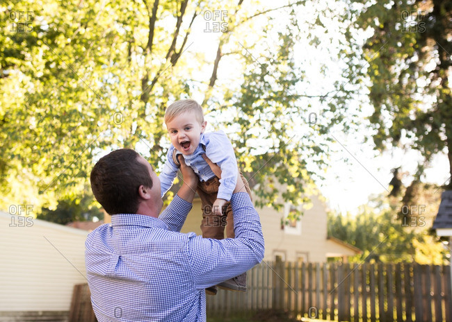 Excited toddler lifted by man in yard