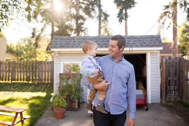 Smiling dad holding toddler in driveway