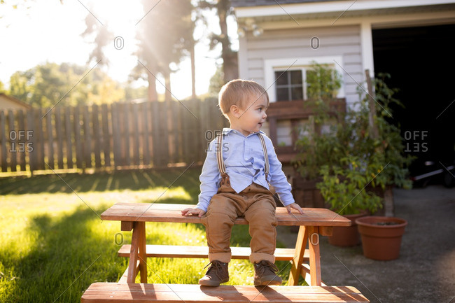 Boy on picnic table in yard