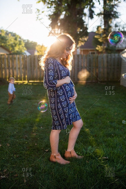 Pregnant woman in sunny yard