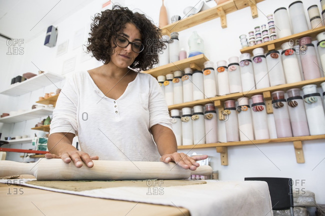 Woman using a roller to work with terracotta in a ceramics workshop