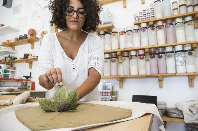 Woman using a leaf to print a draw in terracotta in a ceramics workshop