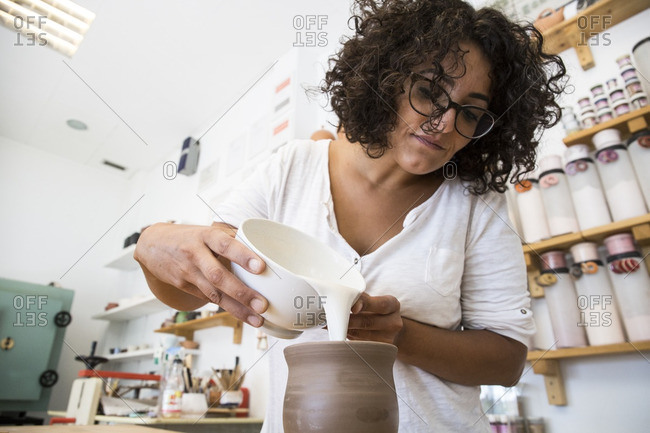 Woman enameling a ceramic mug