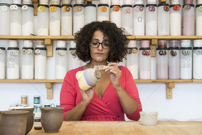 Woman painting a ceramic mug with a brush in her workshop