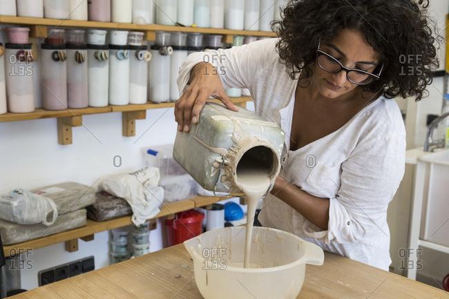 Woman pouring liquid porcelain into a bowl