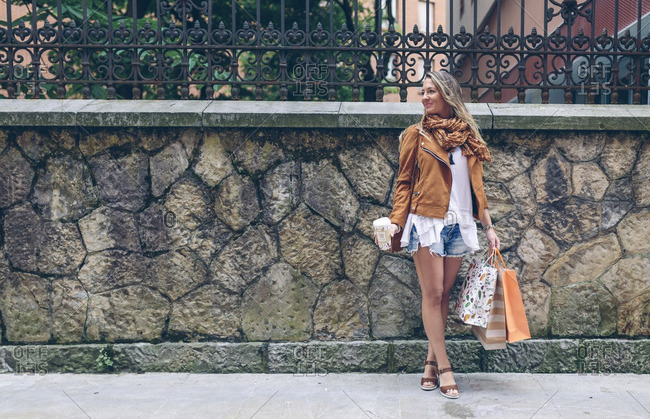 Woman holding shopping bags and takeaway coffee in front of stone wall