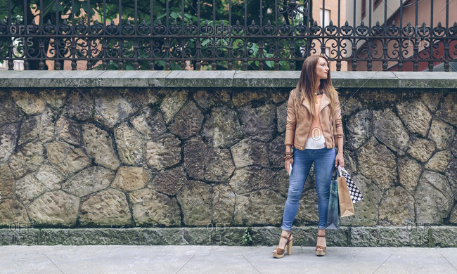 Woman holding shopping bags standing in front of stone wall