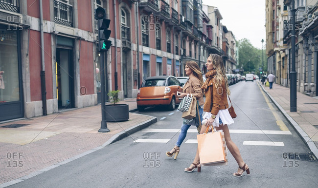 Two women holding shopping bags crossing the street in the city