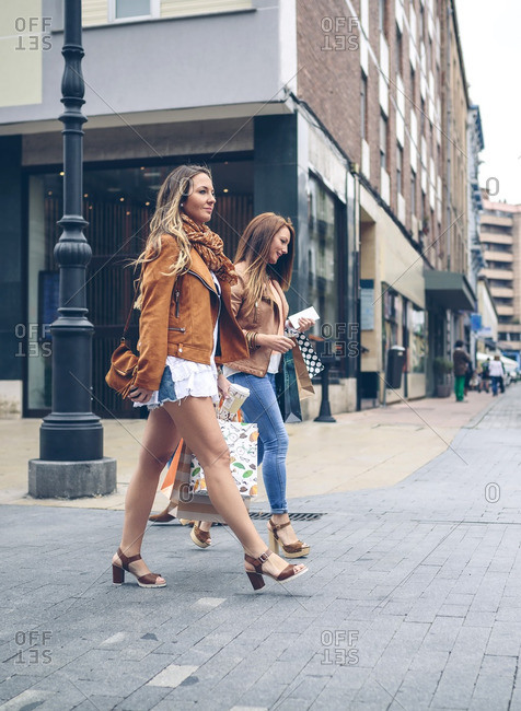 Two women holding shopping bags walking in the city