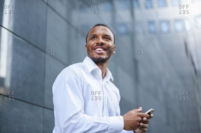 Portrait of content businessman with  cell phone