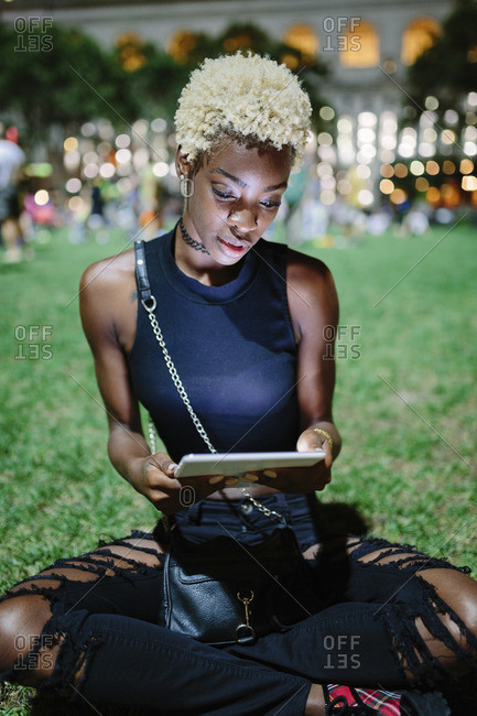 Young woman sitting on meadow of a park at night using tablet