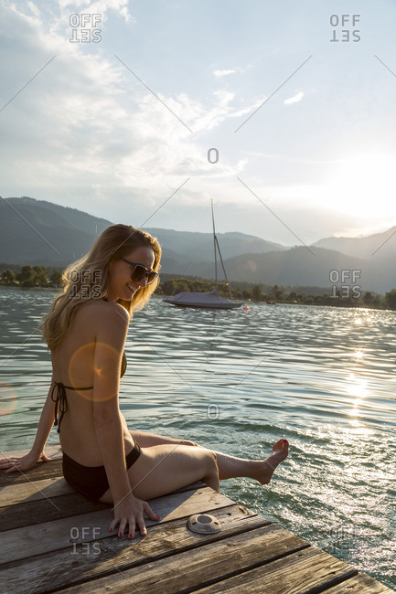 Austria Sankt Wolfgang woman in bikini sitting on jetty at lake