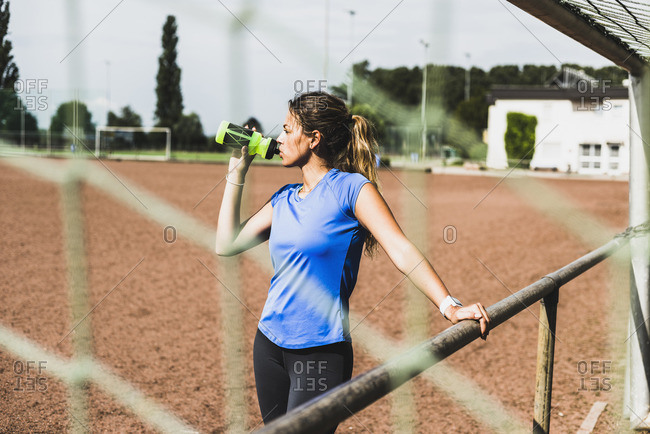Sportive young woman standing on sports field drinking from bottle