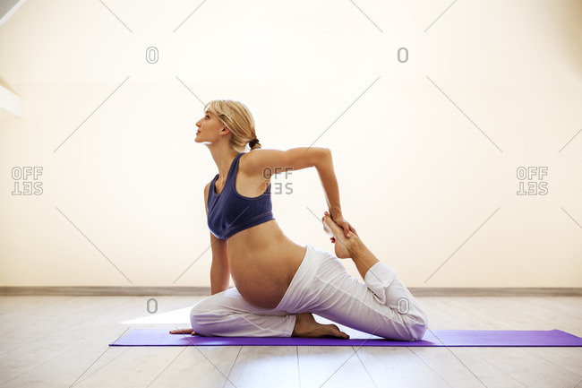 Prenatal yoga woman doing onelegged king pigeon pose