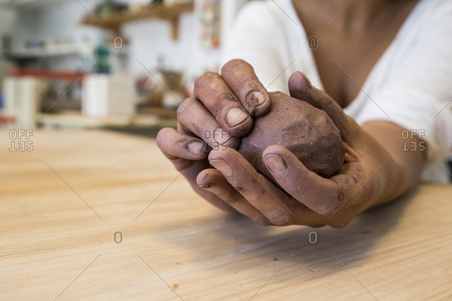 Hands kneading clay in a ceramics workshop