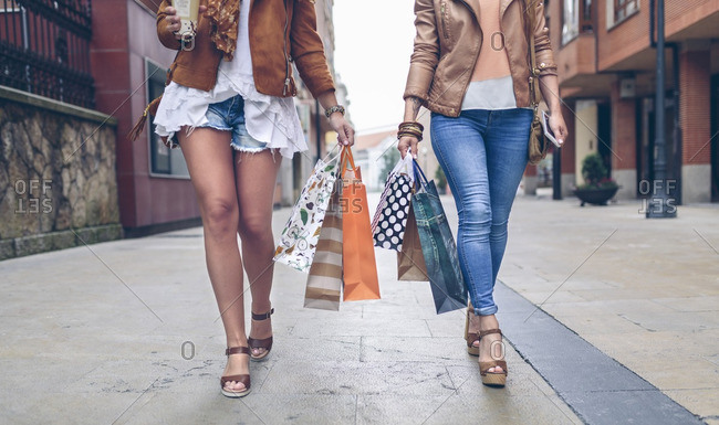 Low section of two women holding shopping bags walking in the city