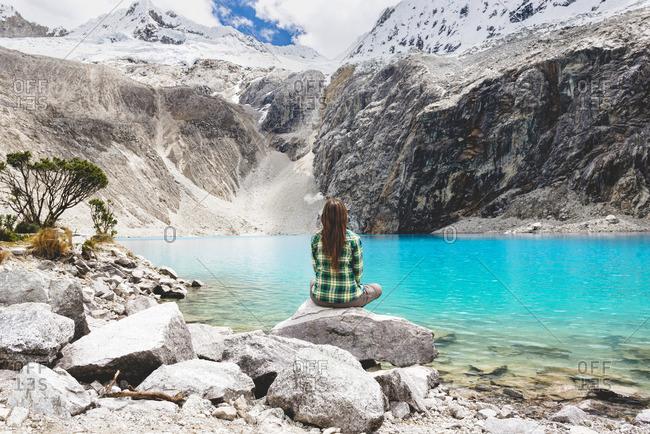Peru Cordillera Blanca Huaraz Huascaran National Park woman sitting at Laguna 69