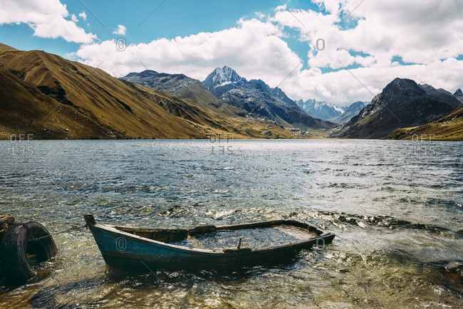 Peru Huaraz wooden boat sunk in a lagoon with Cordillera Blanca mountains in the background