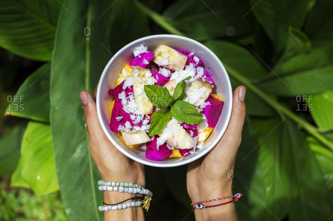 Woman's hands holding bowl of tropical fruit salad