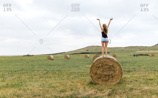 Back view of teenage girl standing on straw bale on a meadow raising arms