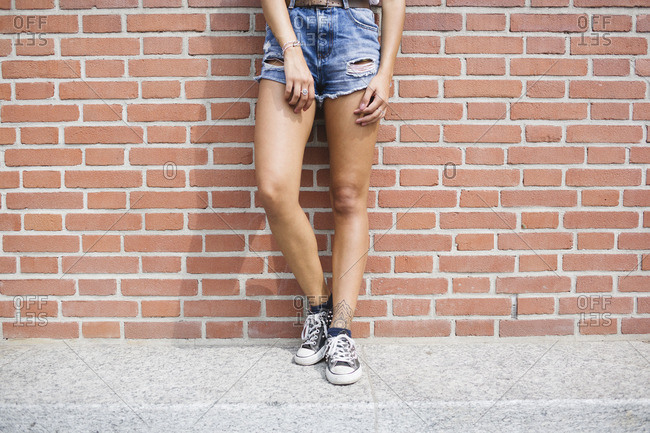 Low section of woman in hot pants leaning against brick wall
