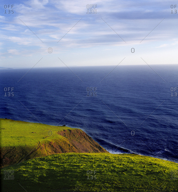 Green cliffs overlooking a deep blue ocean.