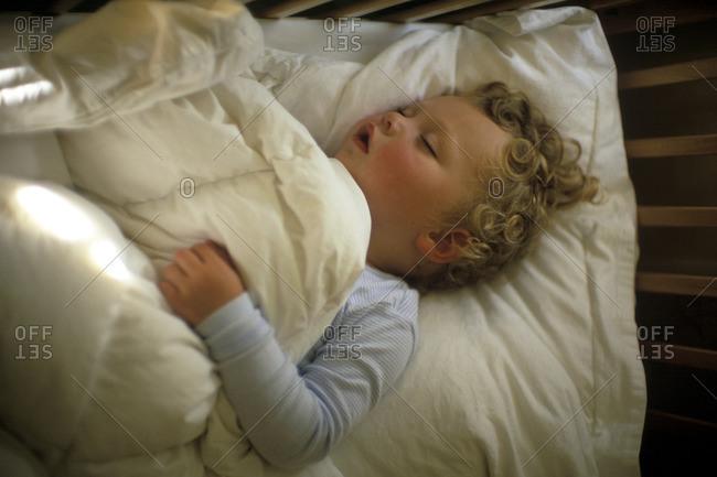 Baby boy sleeping peacefully in his crib.
