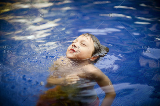 Young boy blowing bubbles in a swimming pool.